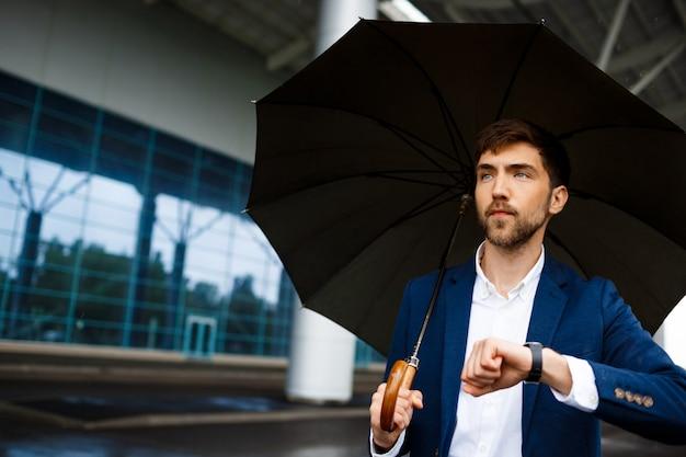 Portrait, Jeune, Homme Affaires, Tenue, Parapluie, Regarder, Montre, Attente Photo gratuit