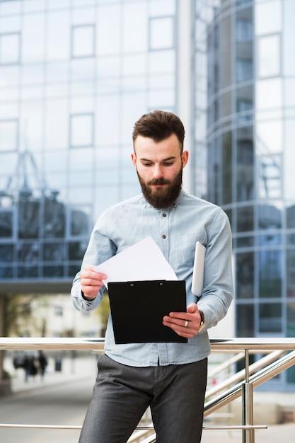Portrait d'un jeune homme d'affaires vérifiant le document devant l'immeuble de bureaux Photo gratuit