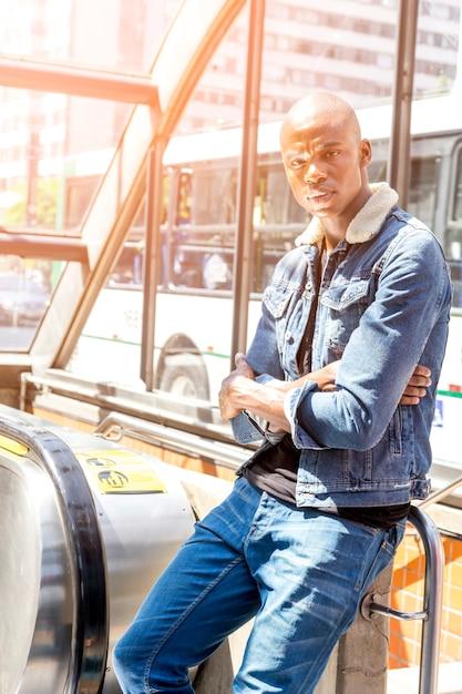 Portrait d'un jeune homme africain debout à l'entrée du métro à la recherche de suite Photo gratuit