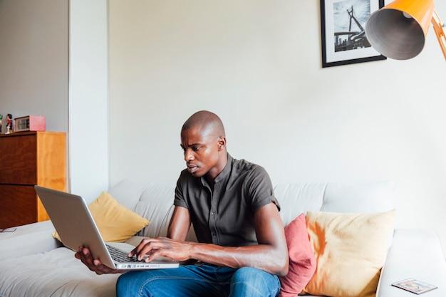 Portrait d'un jeune homme africain utilisant un ordinateur portable à la maison Photo gratuit