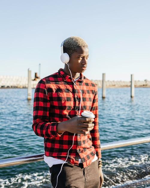 Portrait D'un Jeune Homme Afro-américain, écouter De La Musique Avec Des écouteurs Et Un Café Photo Premium