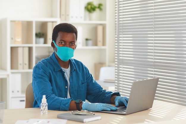 Portrait De Jeune Homme Afro-américain Portant Un Masque Et Des Gants Travaillant Au Bureau Au Bureau Après La Pandémie Photo Premium