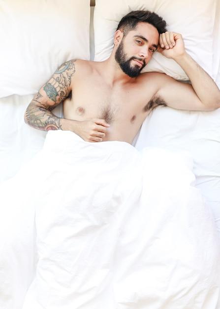 Portrait d'un jeune homme allongé sur un lit Photo gratuit