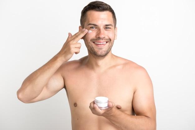 Portrait, de, jeune homme, appliquer, crème visage, sur, debout, contre, fond blanc Photo gratuit