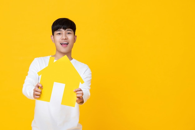 Portrait de jeune homme asiatique heureux tenant le papier à la maison Photo Premium