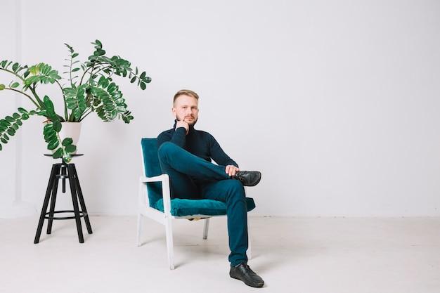 Portrait D'un Jeune Homme Assis Sur Une Chaise Dans Un Bureau Photo gratuit