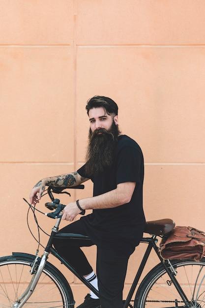 Portrait d'un jeune homme assis sur un vélo en regardant la caméra contre un mur beige Photo gratuit