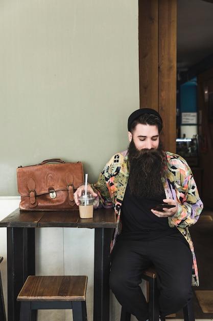 Portrait d'un jeune homme barbu assis dans un café à l'aide de téléphone portable Photo gratuit
