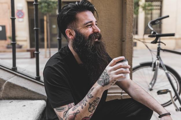Portrait d'un jeune homme barbu assis sur un escalier tenant une tasse à café Photo gratuit