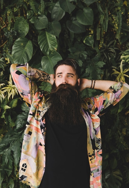 Portrait d'un jeune homme barbu debout devant des feuilles vertes Photo gratuit