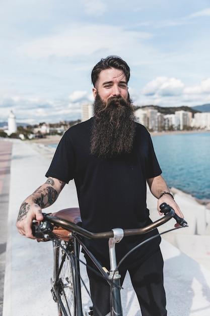 Portrait d'un jeune homme barbu avec son vélo Photo gratuit