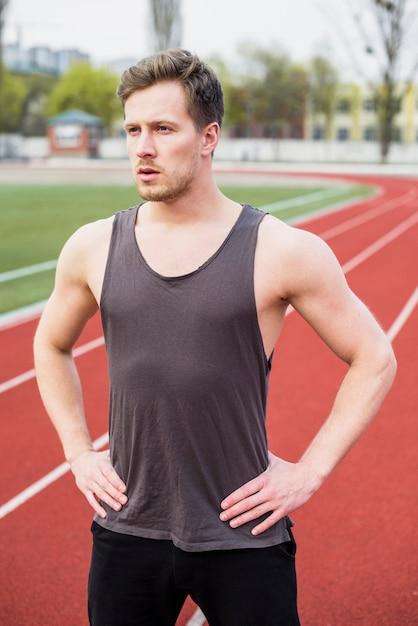 Portrait de jeune homme en bonne santé avec la main sur sa hanche se tenant sur piste Photo gratuit