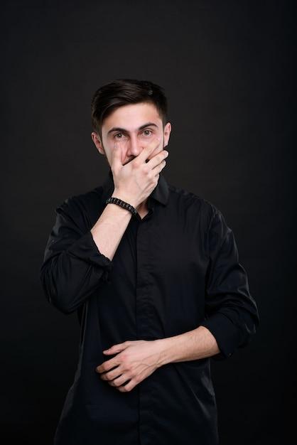 Portrait De Jeune Homme Brune Choqué En Chemise Noire Couvrant La Bouche Avec La Main, Ne Croyant Pas Ses Yeux Photo Premium