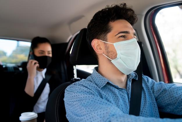 Portrait De Jeune Homme Chauffeur De Taxi Avec Une Femme D'affaires Passager Au Siège Arrière Photo Premium