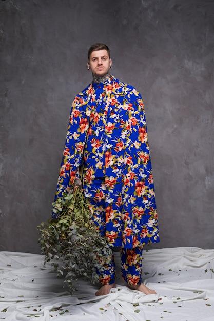 Portrait, de, a, jeune homme, dans, floral, vêtements, tenue, plante verte, brindilles, regarder appareil-photo Photo gratuit