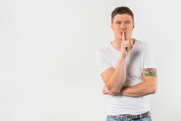 Portrait d'un jeune homme faisant des gestes pour le silence avec le doigt Photo gratuit