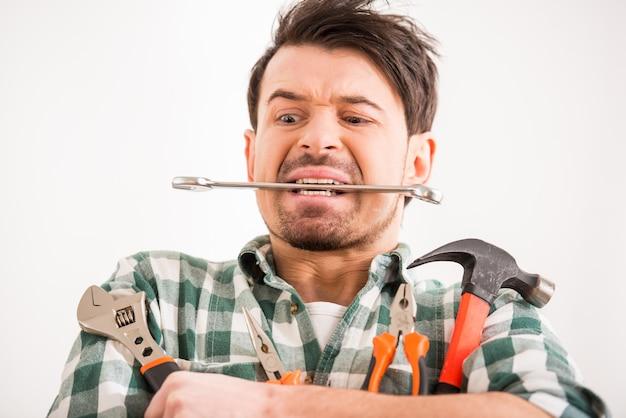 Portrait de jeune homme fait des réparations à la maison avec des outils. Photo Premium