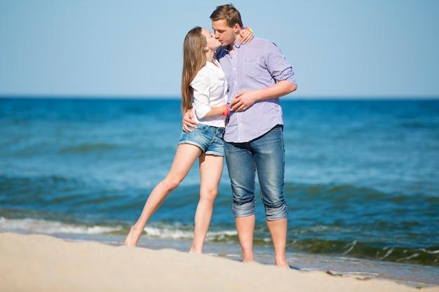 Portrait de jeune homme et femme s'embrasser sur une plage Photo Premium