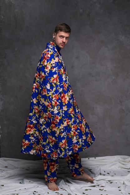Portrait d'un jeune homme hipster avec drapé floral, regardant la caméra contre le mur gris Photo gratuit