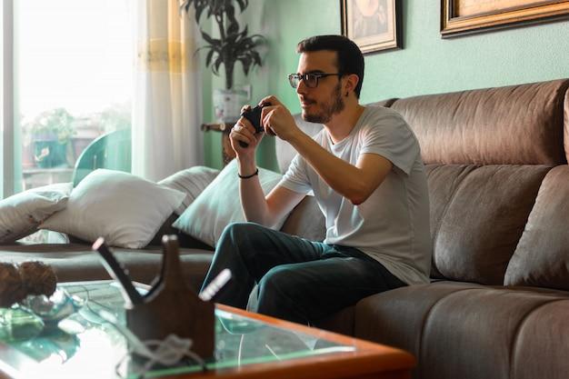 Portrait de jeune homme jouant le jeu vidéo tenant la manette sans fil dans sa maison. Photo Premium