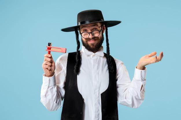 Portrait D'un Jeune Homme Juif Orthodoxe Avec Cliquet Grager En Bois Pendant Le Festival Pourim. Vacances, Célébration, Judaïsme, Tradition, Concept De Religion. Photo gratuit