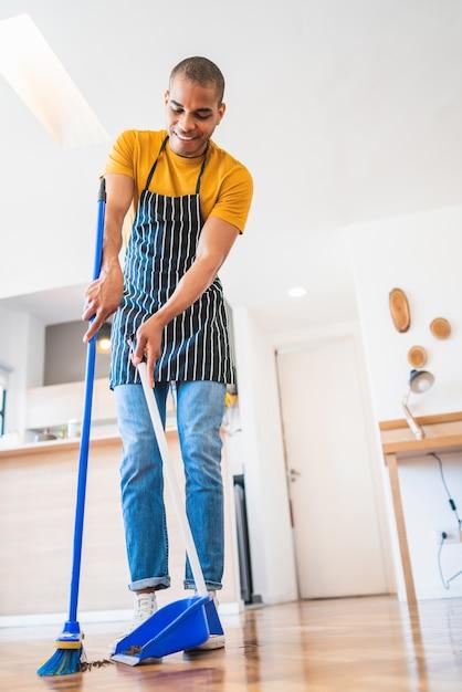 Portrait De Jeune Homme Latin Balayant Le Plancher En Bois Avec Un Balai à La Maison. Concept De Nettoyage, De Ménage Et D'entretien Ménager. Photo Premium