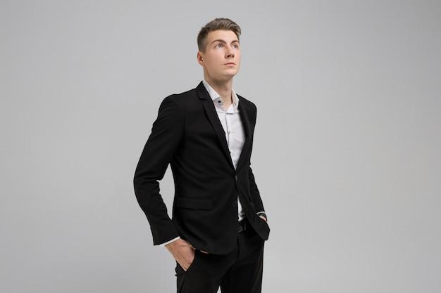 Portrait de jeune homme avec les mains dans les poches en costume noir isolé sur fond blanc Photo Premium