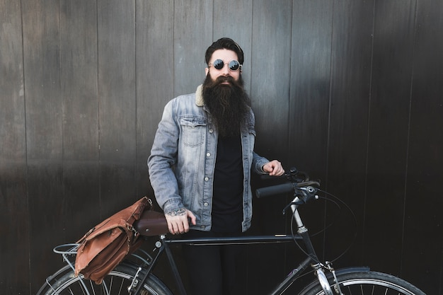 Portrait d'un jeune homme à la mode, lunettes de soleil debout devant un mur en bois noir avec le vélo Photo gratuit