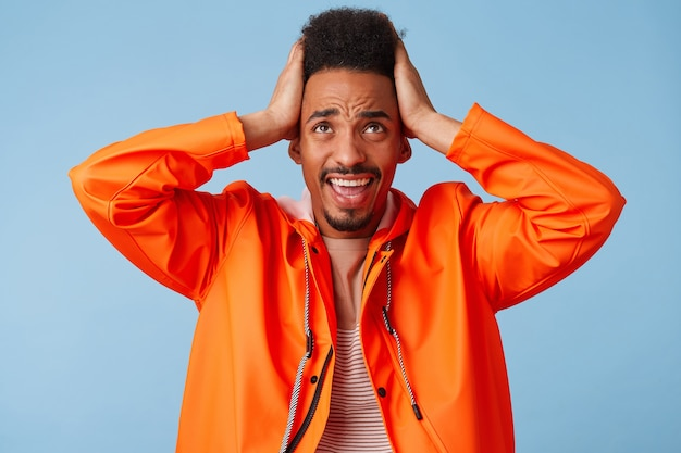 Portrait De Jeune Homme à La Peau Sombre Afro-américaine étonné En Manteau De Pluie Orange, Tenant Sa Tête, A L'air Fou Et Perplexe Face à L'échec. Photo gratuit