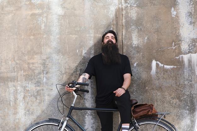 Portrait, jeune, homme, penchant, mur, bicyclette Photo gratuit