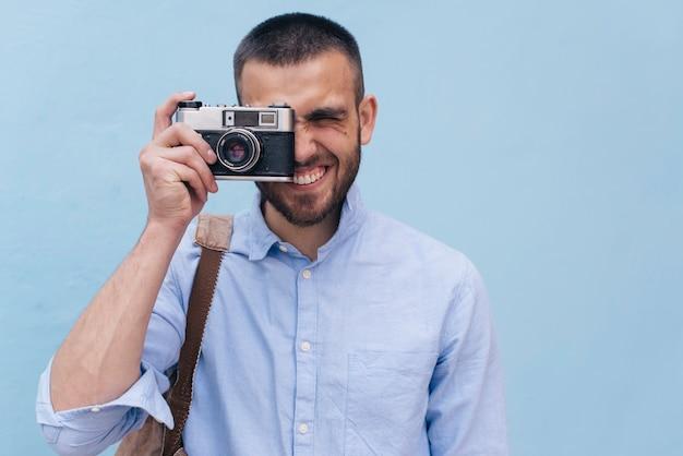 Portrait de jeune homme prenant une photo avec appareil photo rétro Photo gratuit