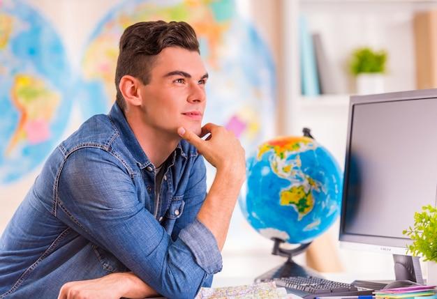 Portrait d'un jeune homme sélectionne pour le voyage à l'aide d'une carte. Photo Premium