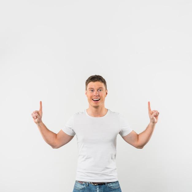 Portrait d'un jeune homme souriant, pointant les doigts vers le haut sur fond blanc Photo gratuit