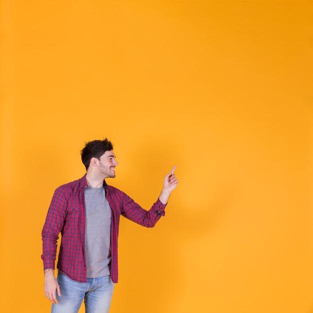 Portrait d'un jeune homme souriant, pointant son doigt sur un fond orange Photo gratuit