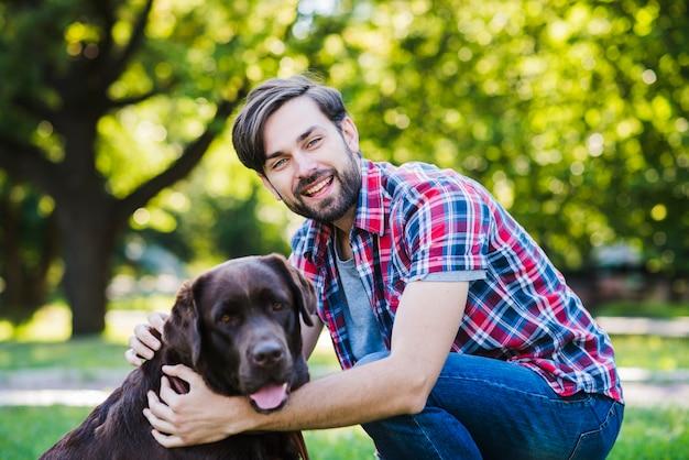 Portrait d'un jeune homme souriant et son chien dans le parc Photo gratuit