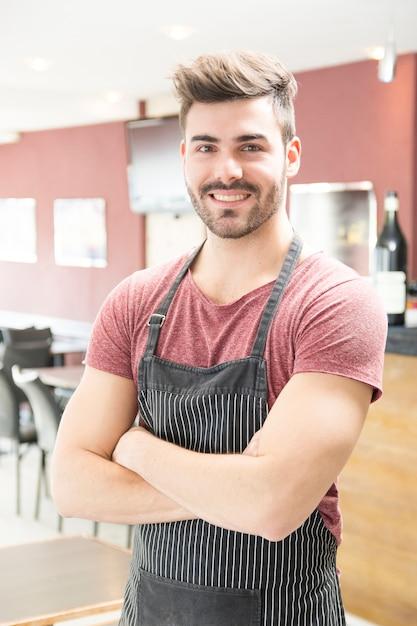 Portrait de jeune homme souriant avec tablier debout dans le bar Photo gratuit