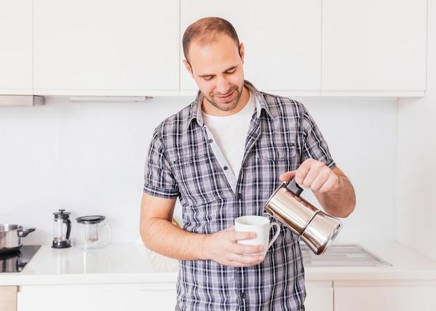 Portrait d'un jeune homme souriant, verser le lait dans la tasse blanche Photo gratuit