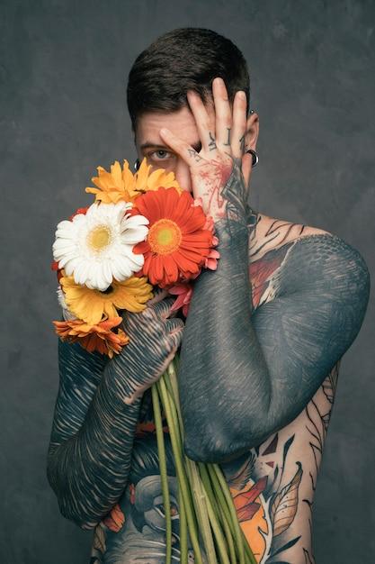 Portrait d'un jeune homme tatoué torse nu tenant des fleurs de gerbera à la main Photo gratuit