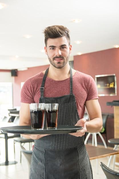 Portrait de jeune homme tenant un plateau dans le restaurant Photo gratuit