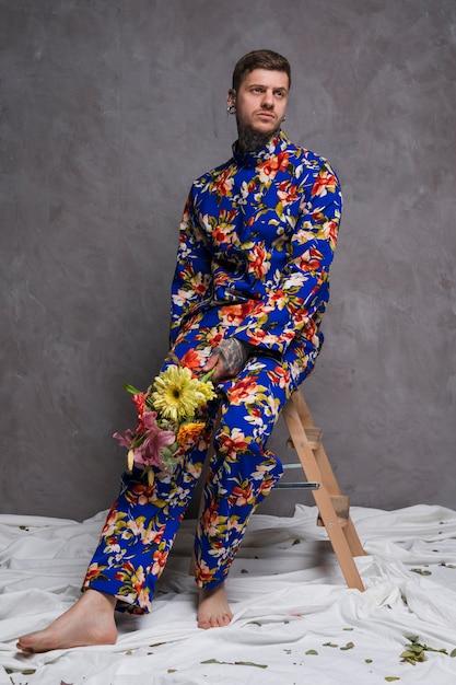 Portrait d'un jeune homme triste assis sur un tabouret avec bouquet de fleurs à la main Photo gratuit