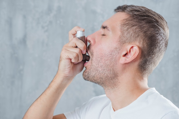 Portrait d'un jeune homme utilisant l'asthme inhalateur sur fond gris Photo gratuit