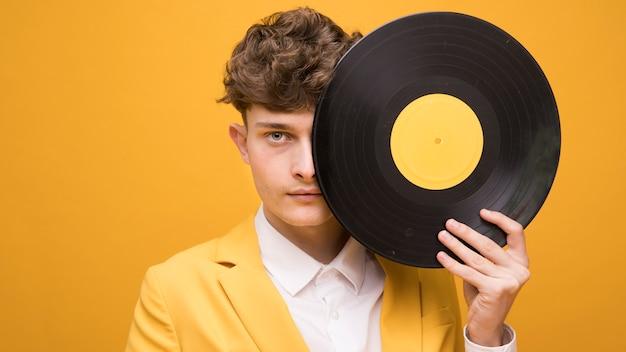 Portrait de jeune homme avec un vinyle dans une scène jaune Photo gratuit