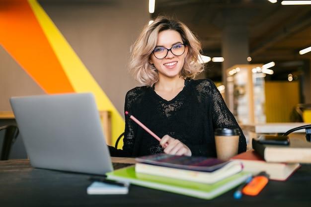Portrait De Jeune Jolie Femme Assise à Table En Chemise Noire Travaillant Sur Ordinateur Portable Au Bureau De Co-working Photo gratuit