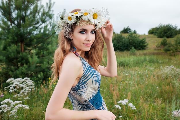 Portrait De Jeune Jolie Femme Avec Un Cercle De Fleurs De Camomille Sur La Tête, à L'extérieur, La Coiffure Photo Premium