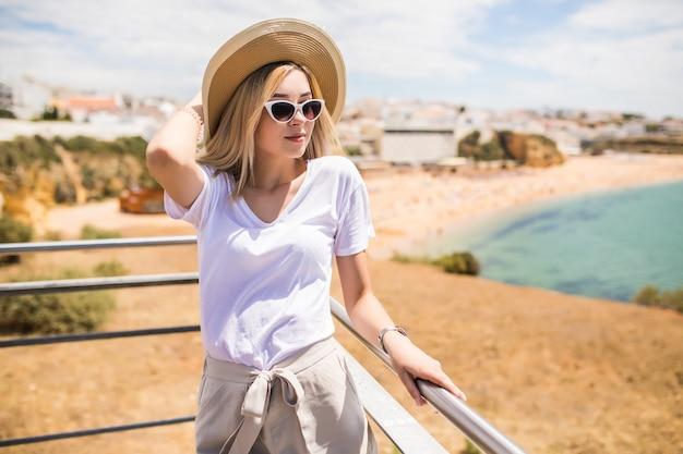 Portrait De Jeune Jolie Femme Avec Chapeau Et Lunettes De Soleil Sur Le Dessus Près De La Plage Photo gratuit