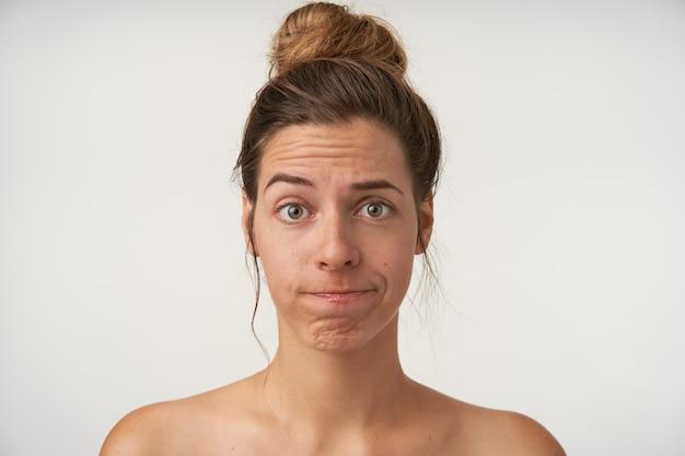 Portrait De Jeune Jolie Femme à La Recherche De Sourcils Levés Et De Lèvres Tordues, Portant Une Coiffure Chignon Haut Et Pas De Maquillage, étant Déçu Photo gratuit