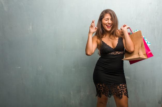Portrait de jeune jolie femme vêtue d'une robe contre un mur qui se croise les doigts Photo Premium