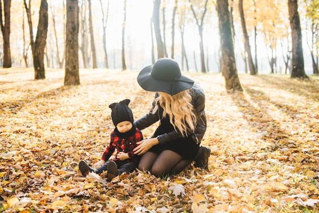 Portrait D'une Jeune Maman élégante Avec De Jeunes Enfants Dans Le Parc Automne. Photo Premium