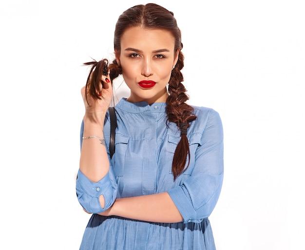 Portrait De Jeune Modèle Femme Souriante Heureuse Avec Maquillage Lumineux Et Lèvres Rouges Avec Deux Nattes En Mains En Robe Bleue Colorée D'été Photo gratuit