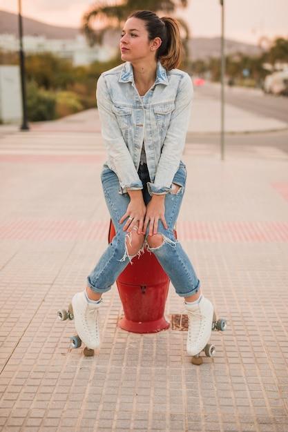 Portrait d'une jeune patineuse assise sur le trottoir Photo gratuit
